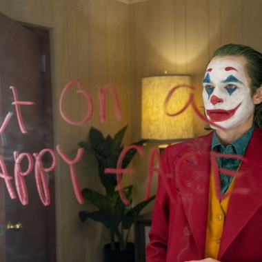 Arthur Fleck (Joaquin Phoenix) dressed as a clown stares into a mirror with