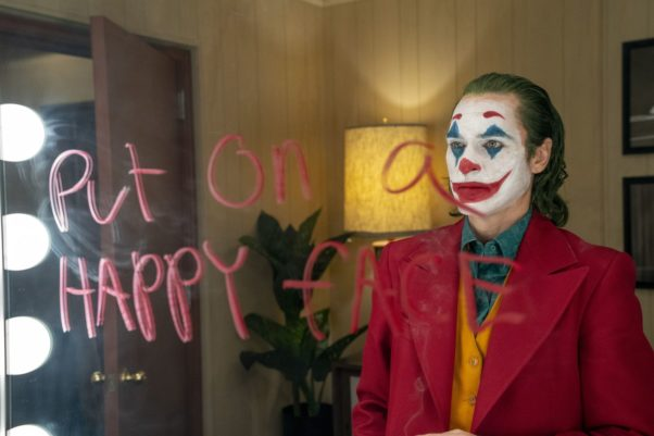 """Arthur Fleck (Joaquin Phoenix) dressed as a clown stares into a mirror with """"Put on a happy face"""" written on it in lipstick. (Photo: Warner Bros. Pictures)"""