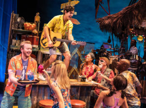 The cast gathers around a bar while a man in a yellow Hawaiian shirt plays guitar and sings on the bar. (Photo: Matthew Murphy)