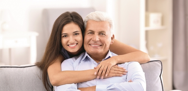 Younger woman with arms around older man who is sitting on a couch. (Photo: Shutterstock)