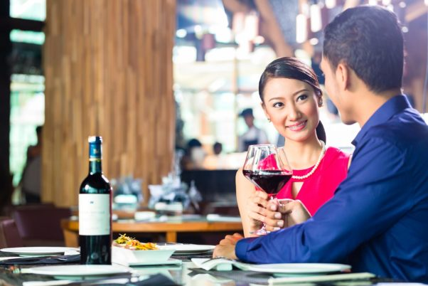 Asian couple having dinner in a restaurant holding glasses of red wine. (Photo: 123RF)