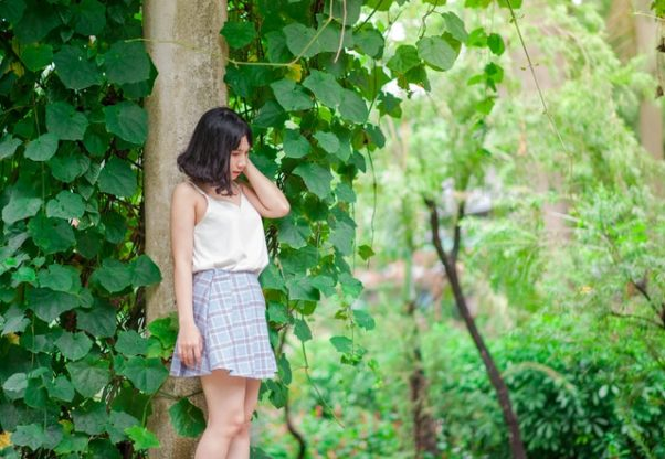 Asian woman in white shirt and gray skirt standing beside a tree. (Photo: Min An)