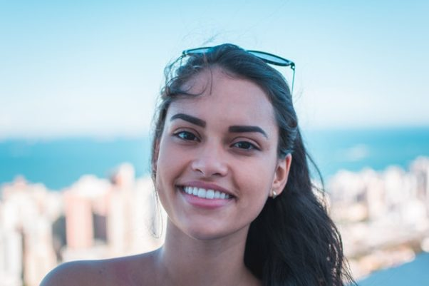 Brazilian woman at the beach smiling. (Photo: Daniel Xavier/Pexels)