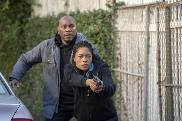 "Milo ""Mouse"" Jackson (Tyrese Gibson) follows police officer Alicia West (Naomie Harris) beside a fence with her gun drawn. (Photo: Sony Pictures)"