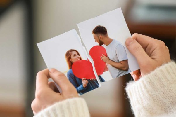 Woman's hands holding a ripped photo of a man and woman holding a large red heart. (Photo: Adobe Stock)