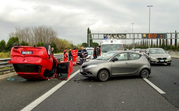 car accident on the highway with a gray car with dented up front end and red car flipped on its roof. (Photo: Valter Cirillo/Pixabay)