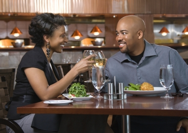 African-American couple dining out. They are toasting with glasses of white wine and smiling. (Photo: Bigstock)