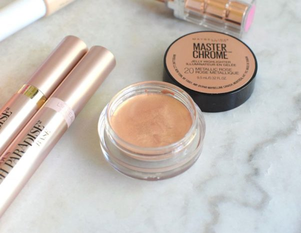 Maybelline Master Chrome Jelly Highlighter Face Makeup and L'Oreal Paris Voluminous Lash Paradise Mascara Primer/Base laying beside each other on a white marble counter. (Photo: Christine Miksell)