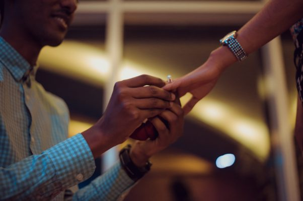 Man putting a ring on a woman's finger. (Photo: Gift Habeshaw/Unsplash)