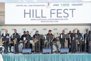 A band performs on a stage under a Hill Fest banner. (Photo: Hill Fest)