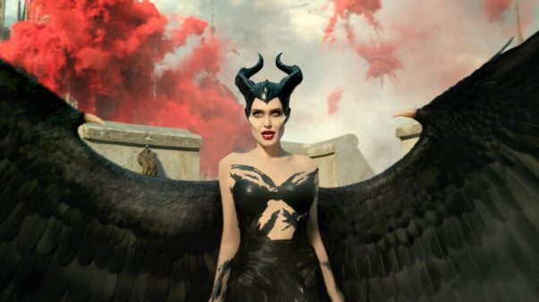 Angelina Jolie dressed as Maleficent with red smoke in the background. (Photo: Walt Disney Studios)