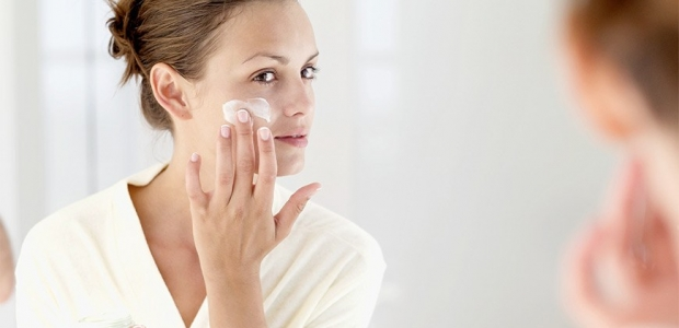 Woman applying moisturizer to her face. (Photo: Stockbyte)