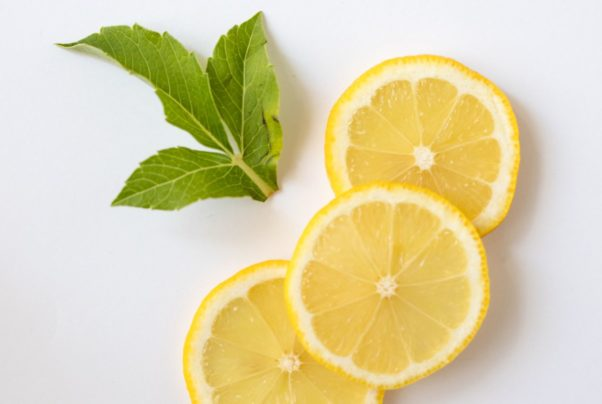 Three slices of lemon and leaves lyig on a white surface. (Photo: Sarah Gualteri/Pexels)