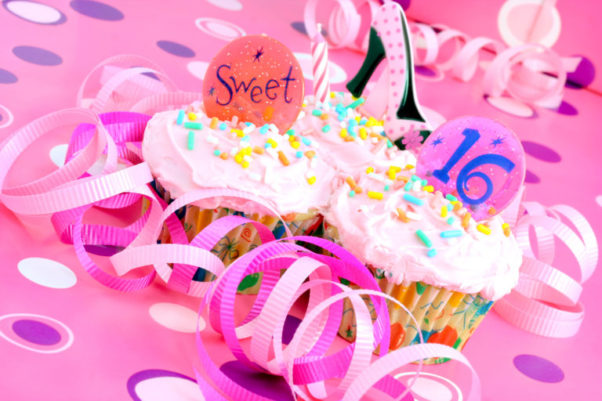 Two pink cupcakes, one with sweet on top and the other with 16 on top. There is confetting scattered around. (Photo: iStock)