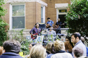 A band of 4 men play guitars and a keyboard on a porch while a crowd listens. (Photo: Terrance Doyle)