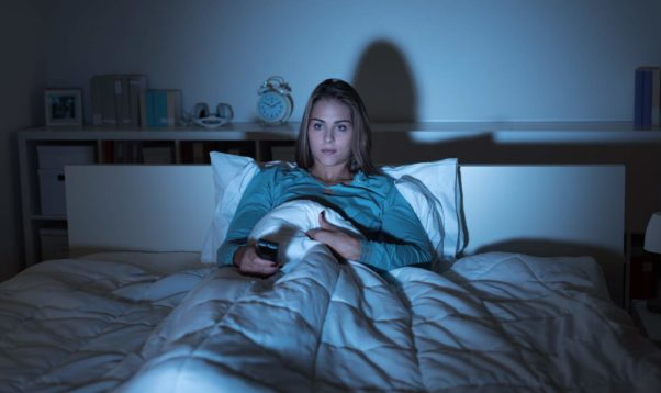 Woman lying in bed at night watching TV in the dark. (Photo: Shutterstock)