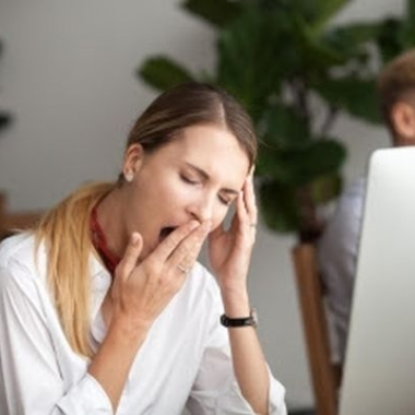 Woman sitting at her computer yawning as she covers her mouth. (Photo: Shutterstock)