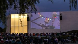 People sitting in lawn chairs outside The Reach watching Nightmare Before Christmas projected onto the side of the building. (Photo: Kennedy Center)