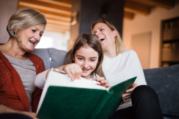A young girl sits between two women on a couch. She holds and pages through a large photo album as the women look on, smiling. A bookshelf and window are in the background. (Photo: Getty Images)