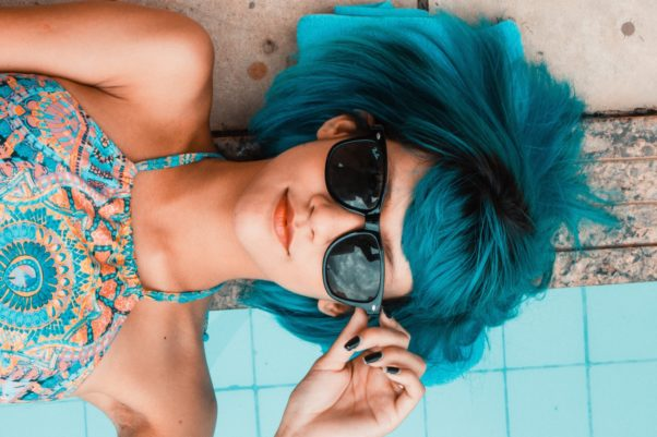 Woman with turquoise-colored hair wearing sunglasses (Photo: Daniel Sampaio/Pixabay)