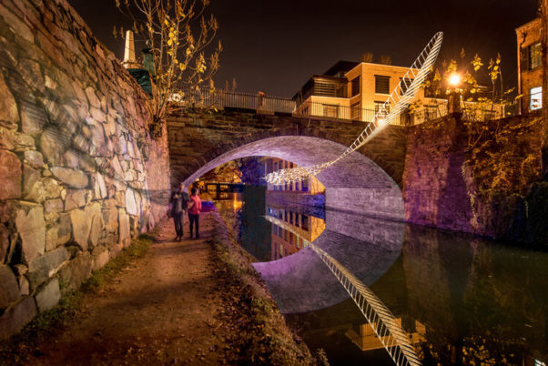A huge hand-crocheted lace feather hangs abot the C&O Canal from under the bridge. (Photo: Sam Kittner and Choi & Shine)