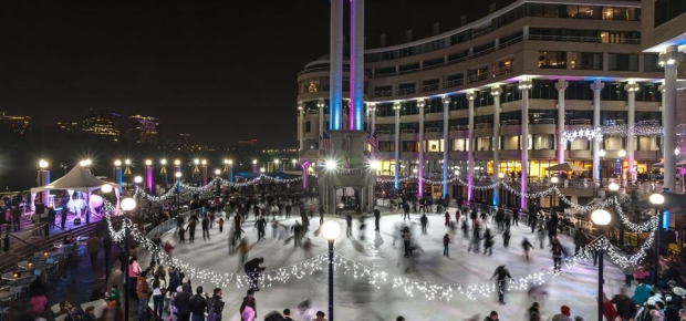 Ice skaters at Washington Harbor fill the rink, which is illuminated in blue and purple with white lights lining the rink. (Photo: Washington Harbour)