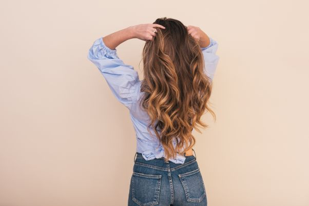 Woman with long brown hair from behind running her fingers through her hair. (Photo: Arnel Hasanovic/Unsplash)