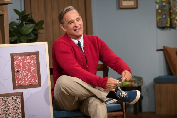 Fred Rogers (Tom Hanks) in his trademark red cardigan sweater puts on his sneakers. (Photo: Sony Pictures)
