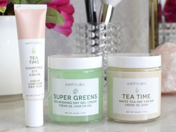 Tea Time Anti Aging Eye Cream, Super Greens Nourishing Day Gel Cream and Tea Time Anti Aging White Tea Day Cream on a white marble counter in front of a dark red flower and a container with makeup brushes in it. (Photo: Christine Mikesell)