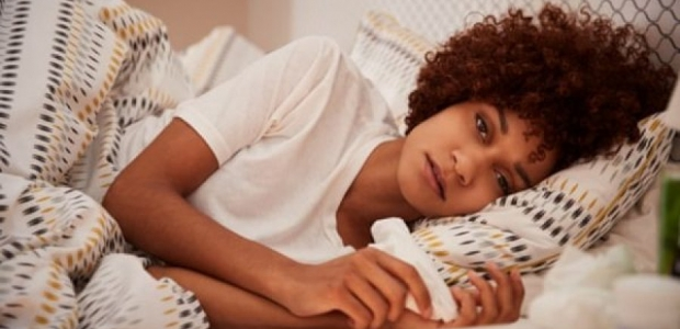 African American woman lying in bed on her side holding a tissue. (Photo: iStock)