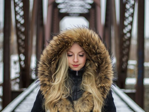 Woman with long blond hair ina fur-lined parka standing on a bridge. (Photo: Guillaume Bolduc/Unsplash)