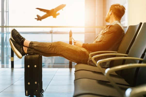 Man sitting along in the airport with his feet propped on his suitcase watching a plane take off our the window. (Photo: jeshoots.com/Unsplash)