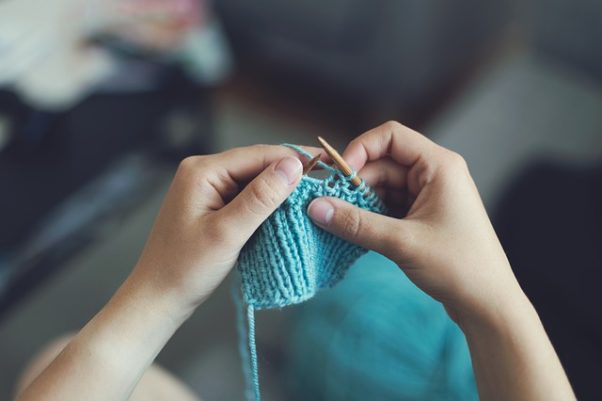 A woman knitting with turquise colored yarn. (Photo: Foundry Co./PIxabay)