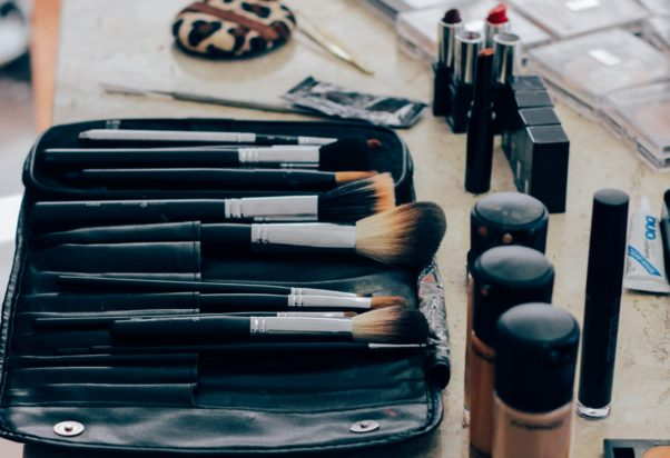 Makeup brushes lying in a case beside different jars and tubes of makeup. (Photo: Manu Camargo/Unsplash)