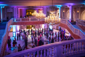 Photo of people at a party at NMWA taken from an upper level with the room lit in purple. (Photo: National Museum of Women in the Arts)
