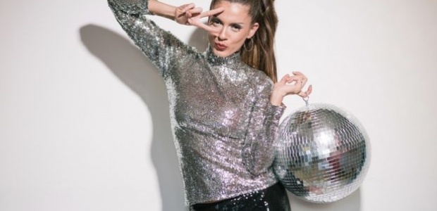 A woman dressed in a silver top holding a disco ball with her fingers in a V over her right eye. (Photo: Shutterstock)