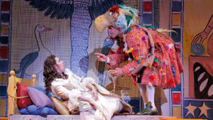 A man dressed as a bird stands over a woman in her bed. (Photo: Kennedy Center)