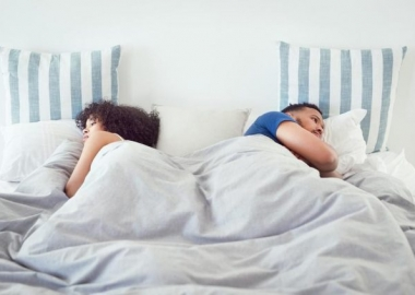 man and woman lying in bed backs to each other. (Photo: Getty Images)
