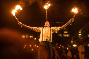 A man balancing flaming batons in both hands and on his forehead. (Photo: Yards Park)