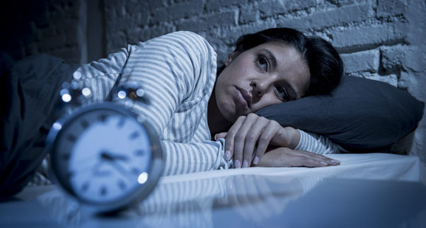 woman lying in bed awake at 3:22 a.m. (Photo: Shutterstock)
