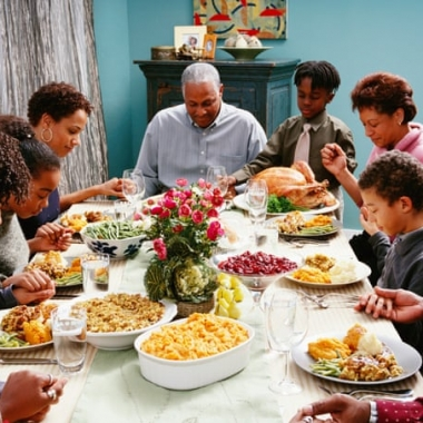 A black family holding hands and praying over a holiday meal with a whole turkey, mac and cheese, and other dishes. (Photo: Corbis)