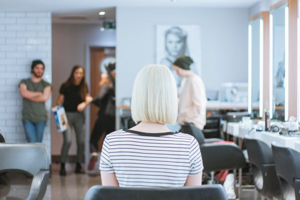 Woman with platinum blond hair from behind sitting in a chair at a salon. (Photo: Toa Heftiba/Unsplash)