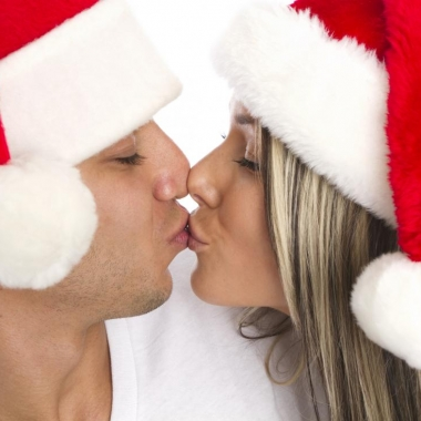 A man and woman in Santa hats kissing. (Photo: Getty Images)