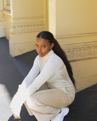 A black woman dressed in white with her hair pulled back squatting down. (Photo: Aysha Sow/Instagram)