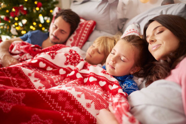 Two children sleep with their parents under a red and white blanket with snowflakes on it. (Photo: Getty Images)
