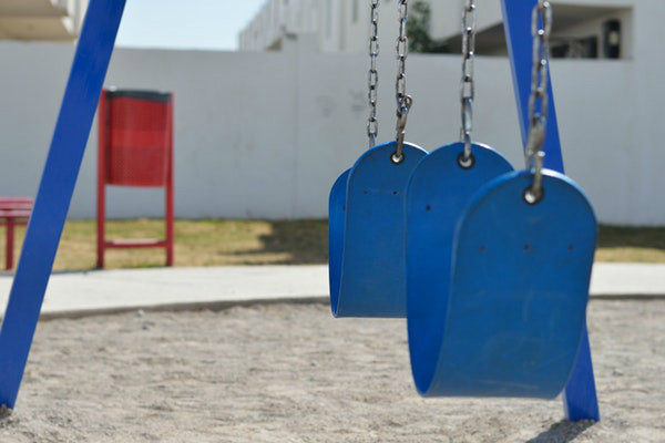 Empty blue swings in a playground. (Photo: Miguel Á. Padriñán/Pexels)