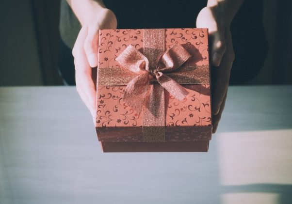 Two hands holding out a present wrapped in dark red paper and a bow. (Photo: Porapak Apichodilok/Pexels)