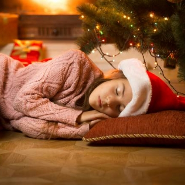 Woman alseep on the floor in front of the Christmas tree wearing a Santa cap. (Photo; 123rf)