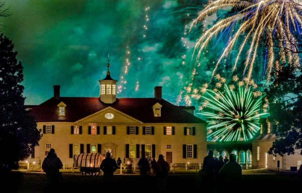 People standing outside in front of the Mount Vernon mansion at night watching fireworks. (Photo: Mount Vernon)