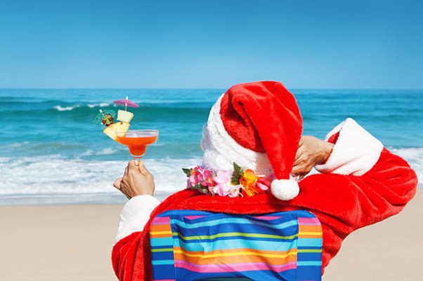 Santa sitting on the beach from behind holding a tropical cocktail. (Photo: Getty Images)